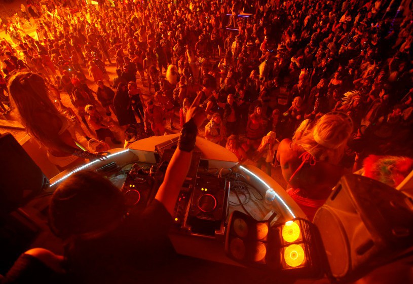 "People dance for a DJ at the Dancetronauts mutant vehicle during the Burning Man 2014 ""Caravansary"" arts and music festival in the Black Rock Desert of Nevada"