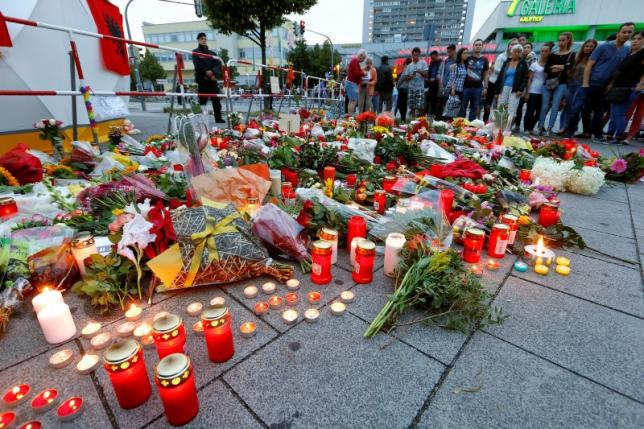 Flowers are laid in front of the Olympia shopping mall, where yesterday's shooting rampage started, in Munich