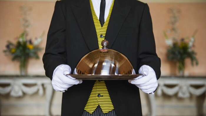 Caucasian butler holding serving tray in formal parlor